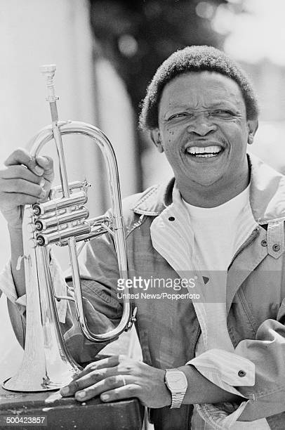 South African trumpet player Hugh Masekela posed holding a trumpet outside Zomba recording studios in Harlesden London on 9th August 1984