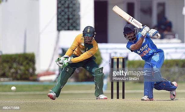 South African wicketkeeper AB de Villiers watches as India A cricketer Manan Vohra plays a shot during the T20 practice match between India A and the...
