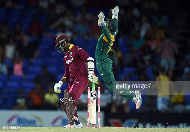 South African wicketkeeper Quinton de Kock leaps in the air to celebrate after taking a catch to dismiss West Indies batsman Marlon Samuels during...