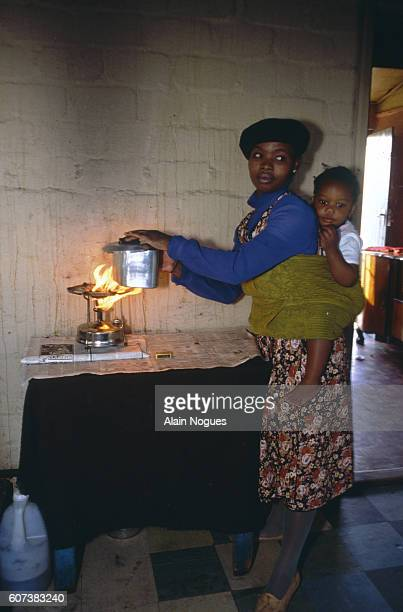 A South African woman carries her baby on her back while she cooks