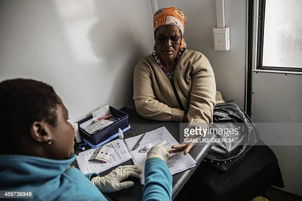 A South African woman gets tested for HIV by an health worker working with Doctors withour borders at a mobile clinic on November 6 2014 in Eshowe...