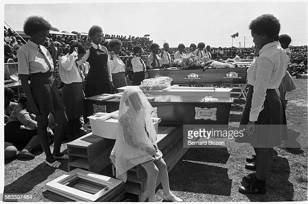 South African women and a little girl stand before coffins with their right fists raised at the funeral of nine people killed during the August 28...