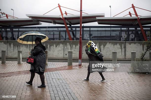 South African women shelter themselves from the pouring rain outside the Orlando Stadium in Soweto on December 10 a few hours before the official...