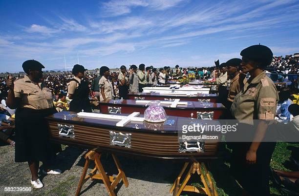 South African women wearing berets and beige shirts stand before coffins and raise their arms at the funeral of nine people killed during the August...