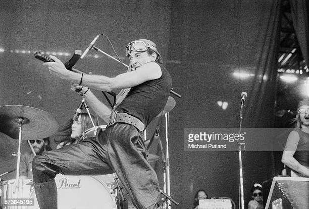 South African writer poet and musician Robert Calvert wielding a dummy sten gun during a concert with English space rock group Hawkwind at Cardiff...