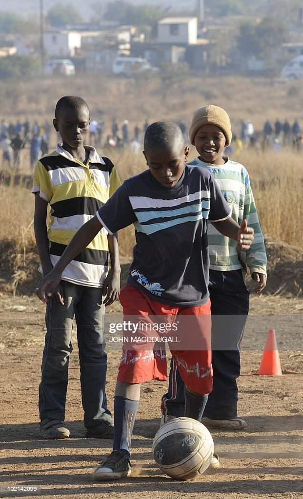 South African youths play with a football at a makeshift field outside the Atteridgeville township near Pretoria on June 16, 2010 as the 2010 World Cup is being held in South Africa.