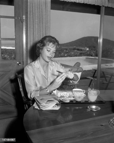 South Africanborn American dancer and actress Juliet Prowse slices fruit at a table in her home Hollywood California 1950s