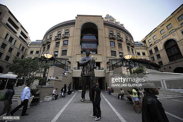 South Africans and tourists walk by the Nelson Mandela giant statue at Mandela Square on May 18, 2010 at Sandton City in Johannesburg, South Africa....