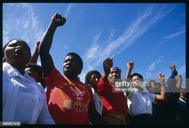 South Africans chant and raise arms at the funeral of nine people killed during the August 28 Gugulethu riots