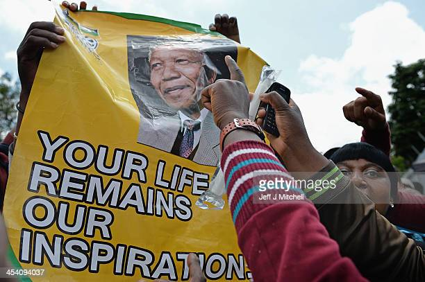 South Africans gather to pay respect and tribute to former President Nelson Mandela outside his Houghton home on December 7 2013 in Johannesburg...