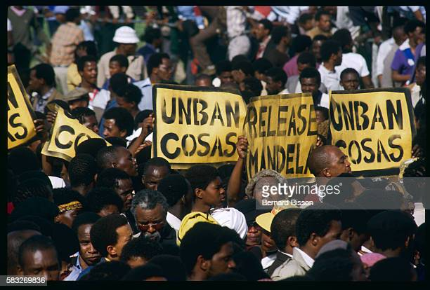 South Africans hold posters at the funeral of nine people killed during the August 28 Gugulethu riots