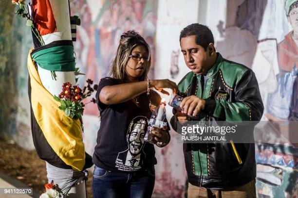 South Africans light candles as they gather at the Old Durban Prison's Human Rights wall to pay their respects to the late South African highprofile...