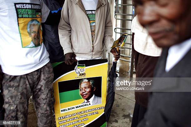 South Africans shelter themselves from the pouring rain while queuing outside the Orlando Stadium in Soweto where a memorial service is supposed to...