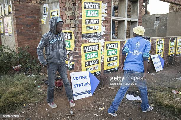 South Africans walk toward a polling station to vote for the general elections early on May 7 2014 in the restive Bekkersdal township Polls opened in...