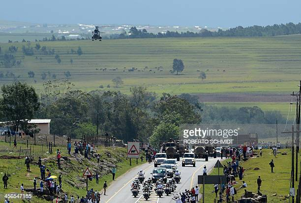 South Africans watch the hearse carrying the coffin of South African former president Nelson Mandela drive through the streets of Mthatha on December...
