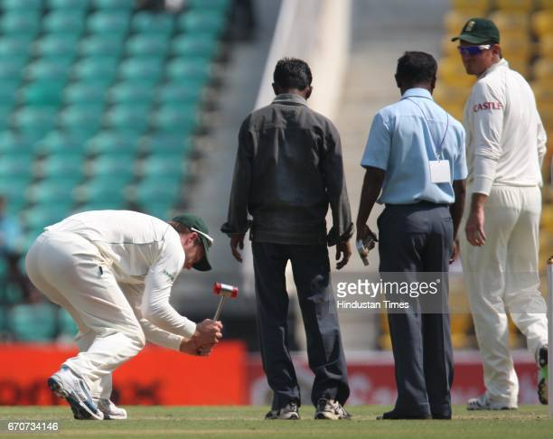 South Africa's AB DeVilliers tries to level the pitch with hammer as captain Graeme Smith looks on during the fourth day of the first test match...