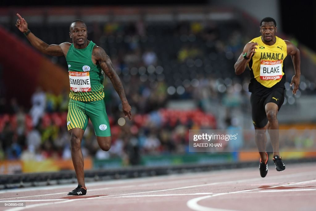 South Africas Akani Simbine and Jamaicas Yohan Blake compete in the athletics men's 100m final during the 2018 Gold Coast Commonwealth Games at the Carrara Stadium on the Gold Coast on April 9, 2018. / AFP PHOTO / Saeed KHAN