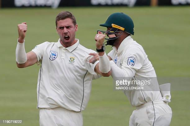 South Africa's Anrich Nortje celebrates with teammates after the dismissal of England's Joe Root during the fourth day of the first Test cricket...