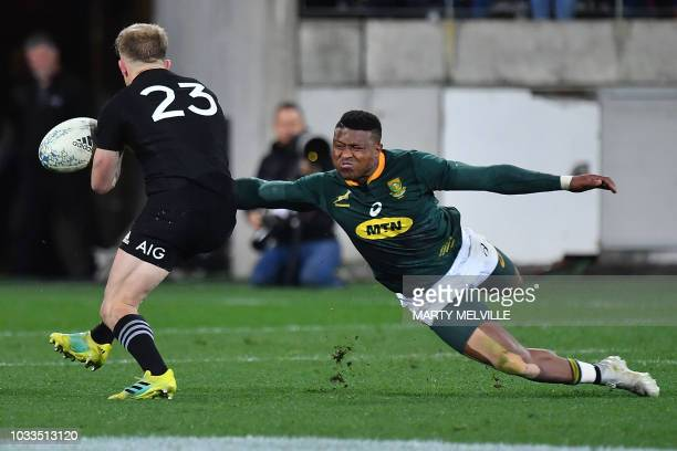 TOPSHOT South Africa's Aphiwe Dyantyi tackles New Zealand's Damian McKenzie during the Rugby Championship match between the New Zealand All Blacks...