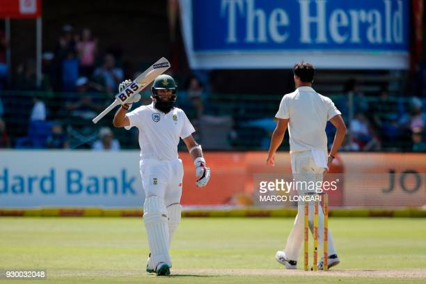 South Africa's batsman Hashim Amla raises his bat to celebrate scoring a halfcentury during day two of the second Sunfoil Cricket Test match between...