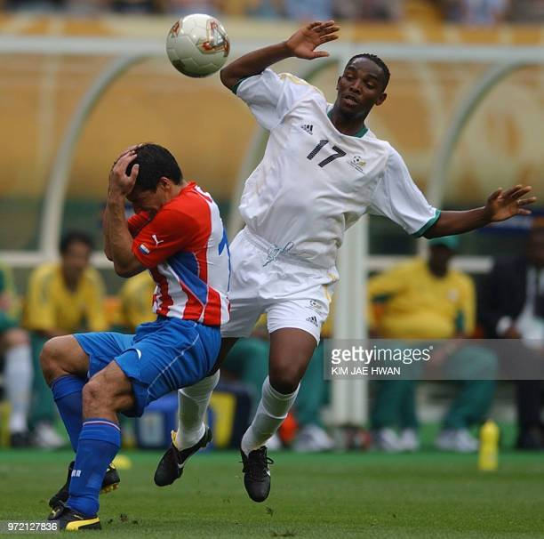 South Africa's Benedict McCarthy and Paraguay's Roberto Acuna vie for the ball 02 June 2002 during their Group B match in Busan AFP PHOTO / KIM...