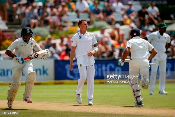 South Africa's bowler Dale Steyn stands as India's batsman Rohit Sharma and Cheteshwar Pujara run during the second day of the first Test cricket...