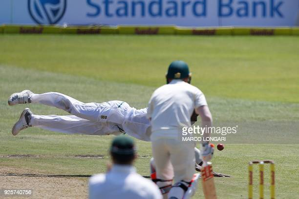 South Africa's bowler Kagiso Rabada dives to catch his own delivery during day one of the first Sunfoil Test between South Africa and Australia at...