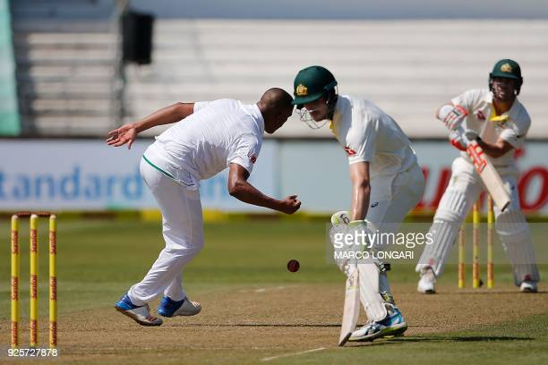 South Africa's bowler Vernon Philander catches his own delivery to Australia batsman David Warner during day one of the first Sunfoil Test between...