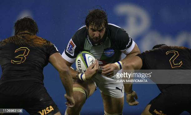 South Africa's Bulls lock Lood De Jager is tackled by Argentina's Jaguares prop Santiago Medrano and hooker Agustin Creevy during their Super Rugby...