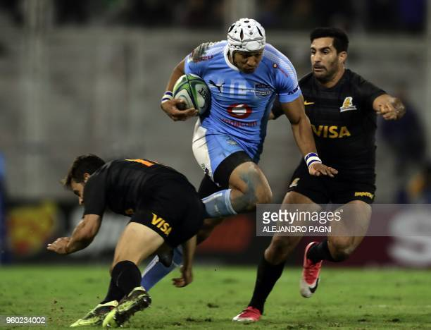 South Africa's Bulls wing Travis Ismaiel runs with the ball between Argentina's Jaguares centre Jeronimo De La Fuente and centre Matias Orlando...