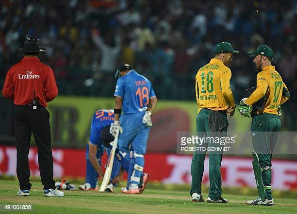 South Africa's captain Faf du Plessis and wicketkeeper AB de Villiers speak during the first T20 cricket match between India and South Africa at The...