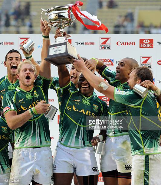 South Africa's captain Frankie Horne Cornal Hendricks and other players celebrate on the podium after their victory in the victory over New Zealand...