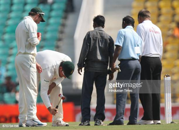 South Africa's captain Graeme Smith tries to level the pitch with hammer as AB DeVilliers looks on during the fourth day of the first test match...