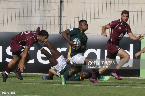 South Africa's center Lasha Lomidze runs for a try despite Georgia's defence during the Under 20 Rugby union World Cup at the Aime Giral stadium in...