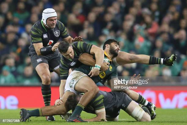 South Africa's centre Damian de Allende is tackled by Ireland's centre Bundee Aki during the autumn international rugby union test match between...
