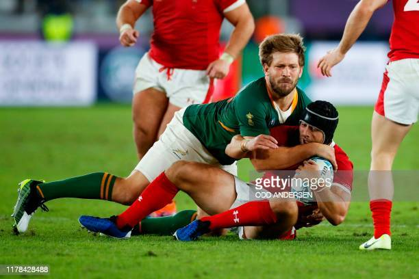 South Africa's centre Frans Steyn tackles Wales' full back Leigh Halfpenny during the Japan 2019 Rugby World Cup semifinal match between Wales and...