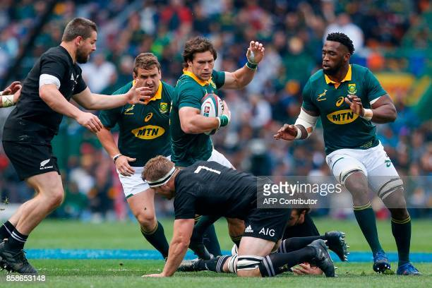 South Africa's centre Jan Serfontein is tackled by New Zealand's blindside flanker Sam Cane during the Rugby test match between South Africa and New...