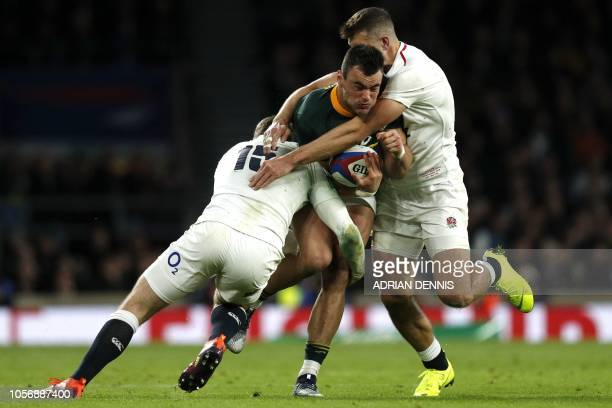 TOPSHOT South Africa's centre Jesse Kriel is tackled by England's fullback Elliot Daly L0 and England's wing Jonny May during the international rugby...