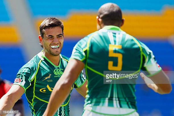 South Africa's Chris Dry congratulates teammate Cornal Hendricks on his try against Canada during their match at the IRB Sevens rugby tournament at...