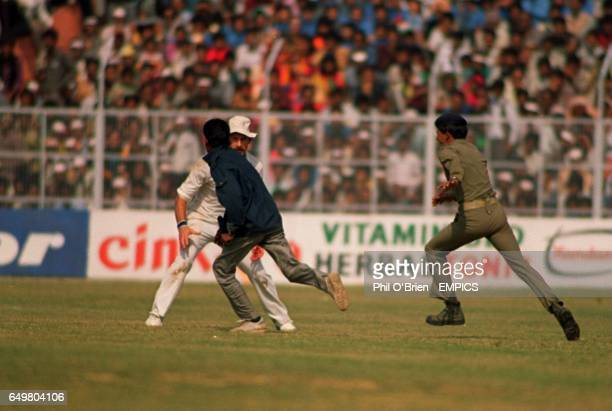 South Africa's Clive Rice tries to stop a pitch invader as police give chase