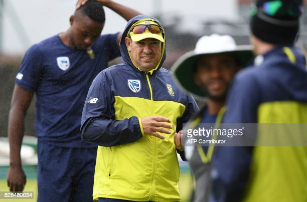 South Africa's coach Russell Domingo heads inside with his players as rain starts to fall during a nets practice session at Old Trafford cricket...