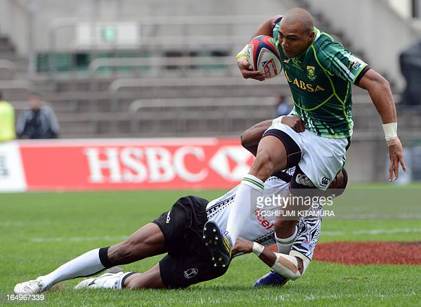 South Africa's Cornal Hendricks carries the ball in front of Fiji's player during their rugby sevens world series Tokyo Sevens 2013 match in Tokyo on...