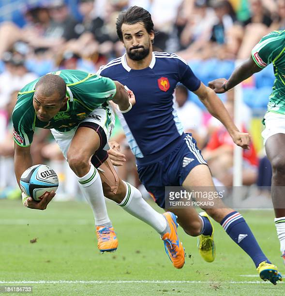 South Africa's Cornal Hendricks gets past Paul Albaladejo of France during their first round match at the IRB Sevens rugby tournament at Skilled Park...