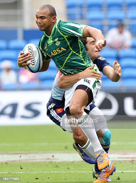 South Africa's Cornal Hendricks is tackled by France's Manoel Dall Igna during their first round match at the IRB Sevens rugby tournament at Skilled...