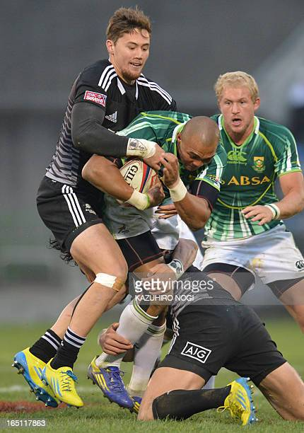 South Africa's Cornal Hendricks is tackled by New Zealand's Gillies Kaka and Ben Lam during their rugby union Tokyo Sevens 2013 final in Tokyo on...