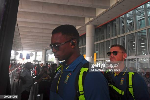 South Africa's cricket player Lungi Ngidi boards a bus upon his arrival at the airport in Kolkata on March 16 2020 India called off its two remaining...