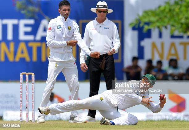 South Africa's Dean Elgar dives as he attempts to field a ball hit by Sri Lanka's Dhananjaya de Silva during the first day of the opening Test match...
