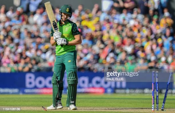 South Africa's Dwaine Pretorius looks down to see a bail flying in the air as he is bowled during the 2019 Cricket World Cup group stage match...