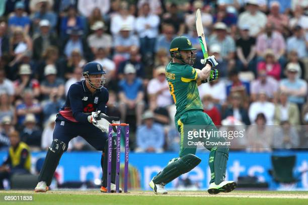 South Africa's Faf du Plessis hits out while England wicket keeper Jos Butler looks on during the Royal London ODI match between England and South...