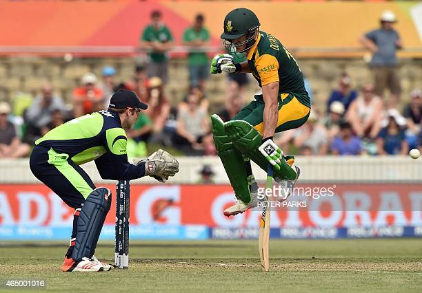 South Africa's Faf du Plessis jumps as Ireland's wicketkeeper Gary Wilson looks on during the 2015 Cricket World Cup Pool B match between Ireland and...
